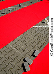 Abstract geometric texture and background with gray stone pavement covered with bright red rubber stripes