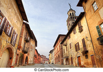 Paved street among historic houses in Saluzzo, Italy.