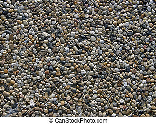 Close-up on a sidewalk tile, showing arranged small stones.