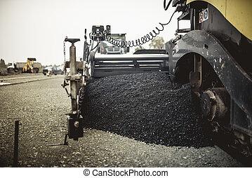 Paver machinery laying fresh asphalt or bitumen during road...