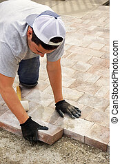 Landscaping concept: man, worker or trade putting down paver stones, vertical