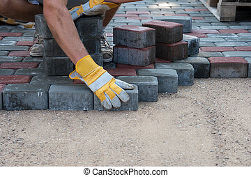 Pavers hands. Mason is building pavement. Hands in yellow gloves lays layers of bricks.