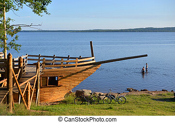 Lake view. On the shore of the pavilion in the form of a sailing ship in the Karelian Isthmus, Russia.