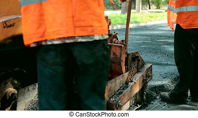 Paving A Road - An asphalt paving machine and road...