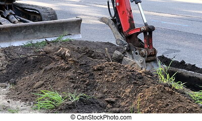 Paving out sewer line machinery for road work, excavating, ...