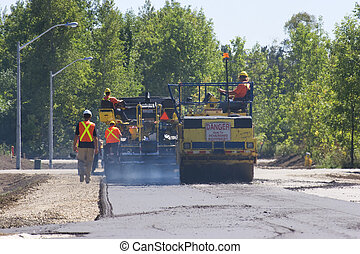 telephoto shot of paving crew paving a new road in a rural foresed new sub division