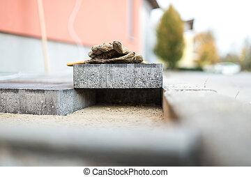 Paving stone resting above newly installed bricks