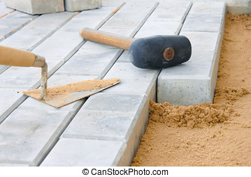 Paving stone - Stone blocks laying down on sand