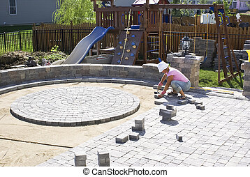 Paving the Patio - Woman with the white hat paving patio at...