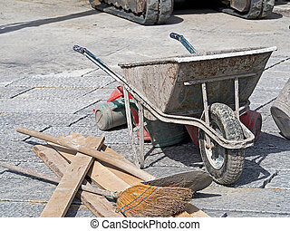 paving work wheelbarrow bucket and broom