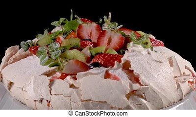 Pavlova cake with fresh blueberries, strawberries and kiwi.