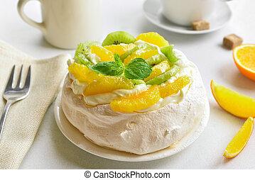 Tasty pavlova meringue cake with kiwi, orange slices and whipped cream.