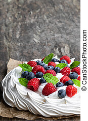 Pavlova meringue nest with berries and mint leaves on wooden table