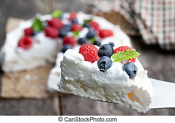 Pavlova meringue slice with berries and mint leaves on wooden table