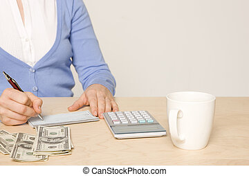 desk with cash, calculator, checkbook, pen and coffee cup