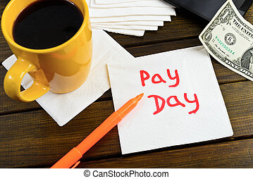 Pay day - motivational handwriting on a napkin with a cup of...