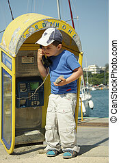 Pay phone - Boy in blue t-shirt calling from old pay phone