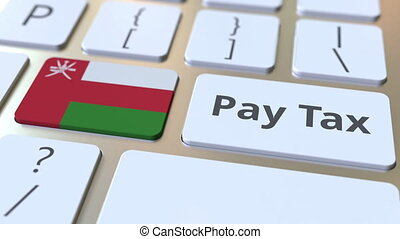PAY TAX text and flag of Oman on the computer keyboard....
