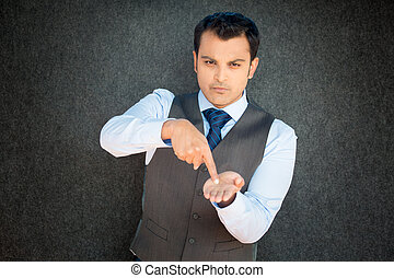 Closeup portrait of mean young man in vest and tie pointing at palm hand, indicating that it is pay day, time to pay up, isolated black gray background