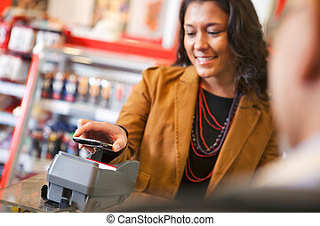 Pay with Cell Phone - Young woman paying for purchase with...