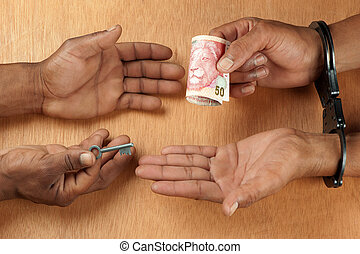 Paying a bribe - One hand receives a bribe whilst the other...