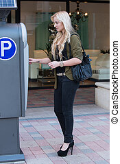 Paying at a parking meter - Young woman model paying...