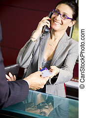 Paying by credit card: young salesclerk smiling at a...