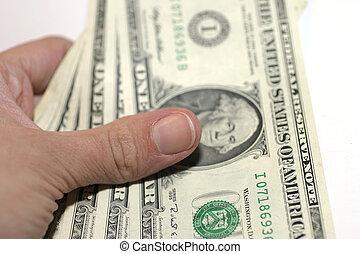 Paying Cash - Holding three 1 Dollar bills. Shallow DOF.