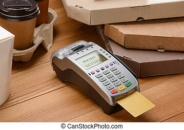 Paying for coffee and pizza. POS terminal with inserted credit card