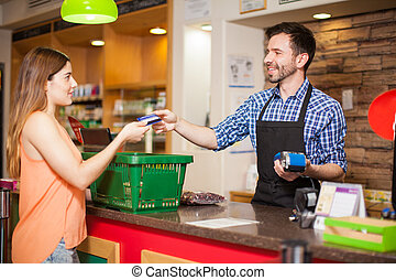 Paying with credit card at a grocery store - Profile view of...