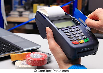 Paying with credit card in an electrical shop, finance concept