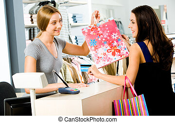 Portrait of shop assistant giving shopping bag to happy woman in the shopping mall
