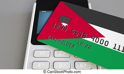 Payment or POS terminal with credit card featuring flag of Jordan. Jordanian retail commerce or banking system conceptual animation
