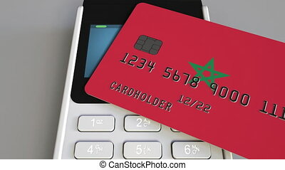 Payment or POS terminal with credit card featuring flag of Morocco. Moroccan retail commerce or banking system conceptual animation