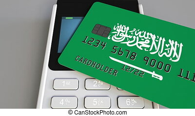 Payment or POS terminal with credit card featuring flag of Saudi Arabia. Retail commerce or banking system conceptual animation