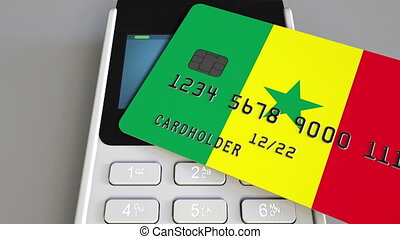 Payment or POS terminal with credit card featuring flag of Senegal. Senegalese retail commerce or banking system conceptual animation
