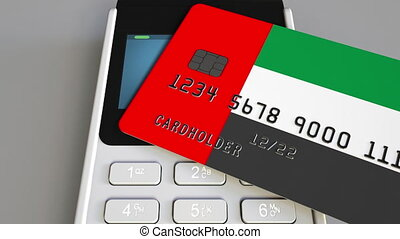 Payment or POS terminal with credit card featuring flag of the United Arab Emirates. UAE retail commerce or banking system conceptual animation