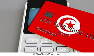 Payment or POS terminal with credit card featuring flag of Tunisia. Tunisian retail commerce or banking system conceptual animation