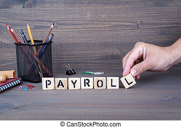 payroll. Wooden letters on dark background - payroll...