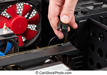 pc engineer hand holding 6 plus 2 pin video card power connector while maintenance