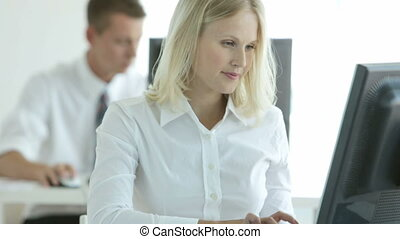 PC operators - Young woman operating pc in office, her...