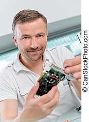 PC repair man holding a graphics card