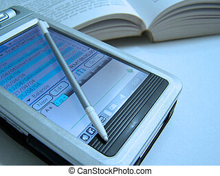 a close up view of PDA that showing financial entries with a book as a background