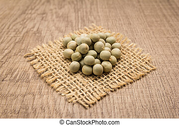 Pea. Grains on square cutout of jute. Wooden table. Selective focus.
