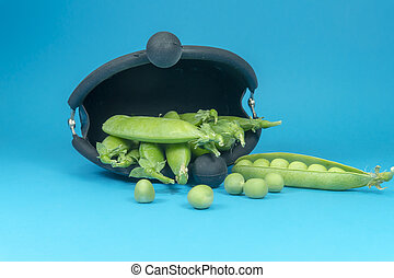 Pea pods and peas spilling from frame purse