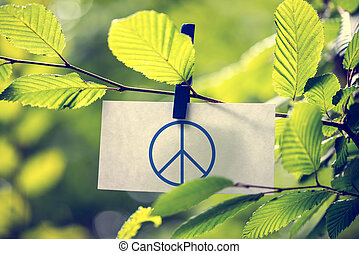 Peace concept with a peace sign attached to a twig of fresh...