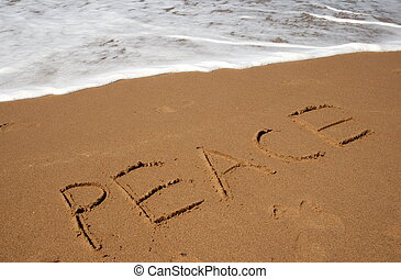 The word Peace written roughly in the sand with the incoming tide rolling in