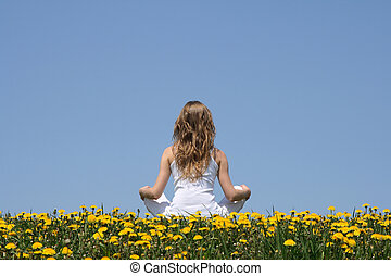 Peace of mind. Longhaired young woman in white clothes relaxing in a flowering dandelion field.