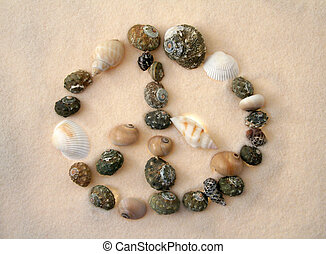 peace sign made of several different sea-shells, sand background