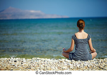 Peace - Young woman sitting on the beach enjoying peaceful...